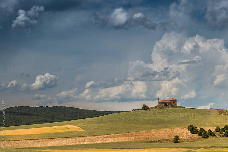 landscape with a church and cloudy sky by Javier Pardina for Stocksy United