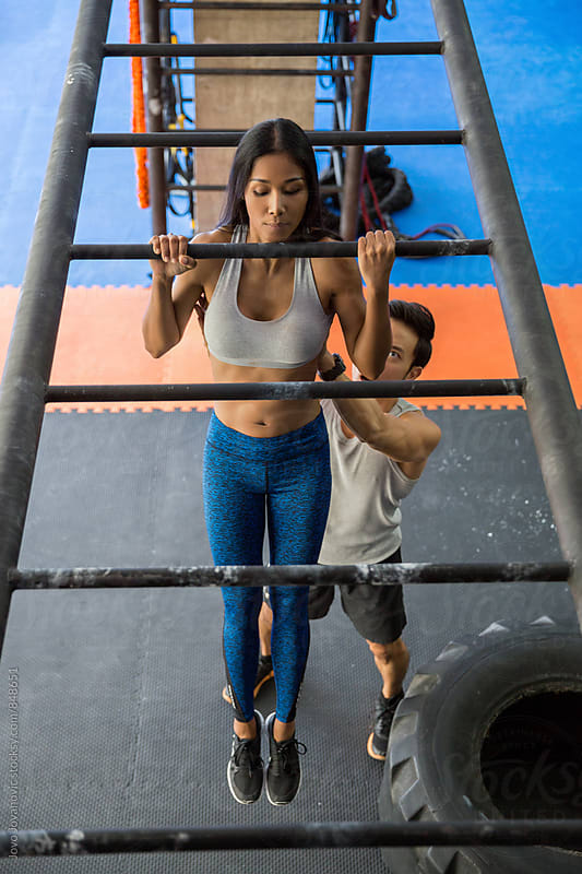 Fit woman doing pull-ups with her instructor by Jovo Jovanovic for Stocksy United