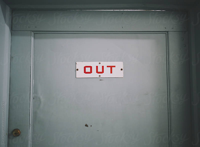 Light blue door with a small sign with the word 'out' written on it. by Lucas Saugen for Stocksy United
