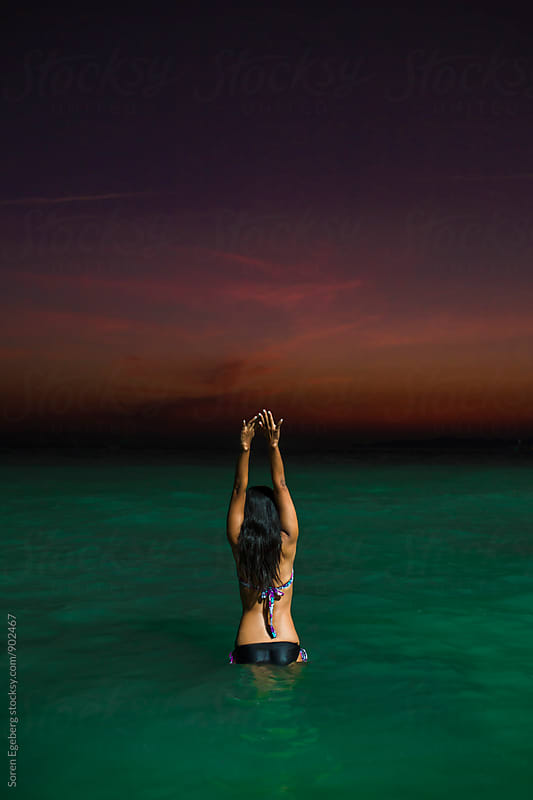 Girl going night swimming in the ocean by Søren Egeberg Photography for Stocksy United
