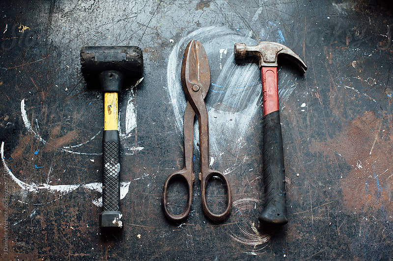 A mallet, tin nippers or wire cutters and hammer on a worn work table. by J Danielle Wehunt for Stocksy United