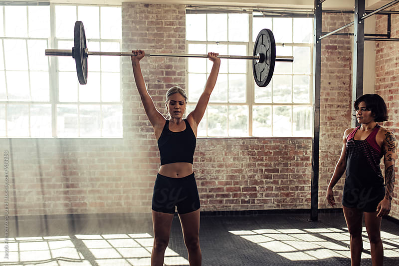 Strong woman with trainer lifting barbell at gym by Jacob Ammentorp Lund for Stocksy United