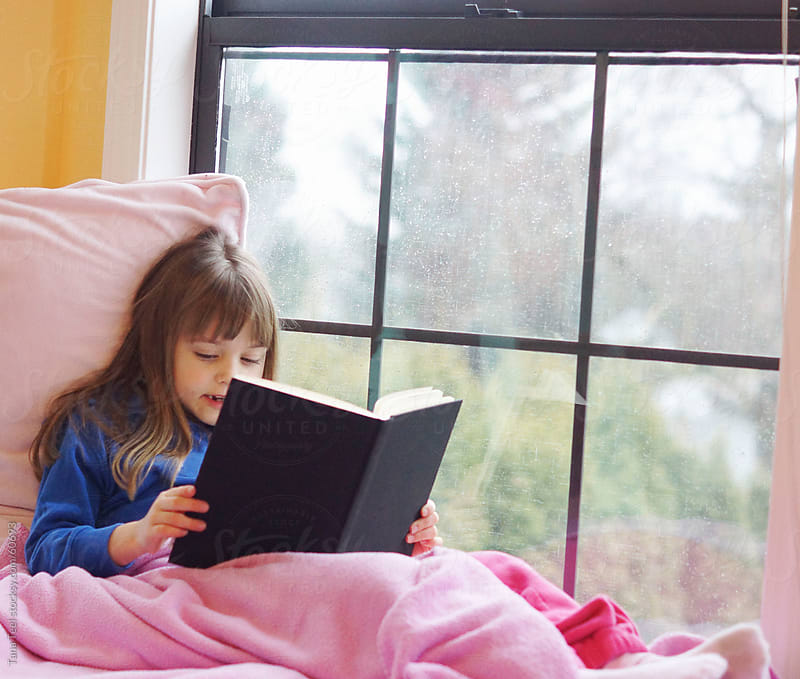 A young girl sits in a window seat reading her book on a rainy day. by Tana Teel for Stocksy United