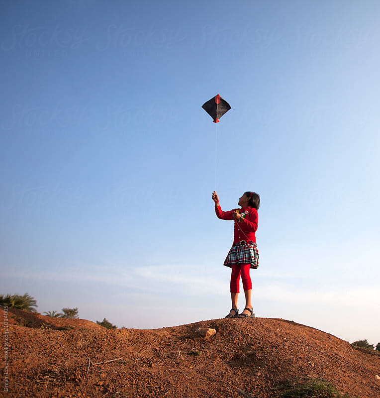 A little girl flying kite by PARTHA PAL for Stocksy United