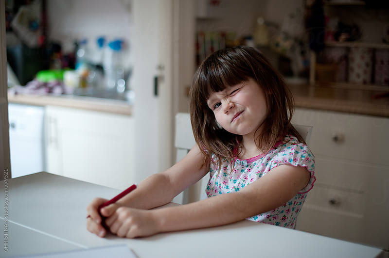 Girl pulling a face at the table by Christina Kilgour for Stocksy United