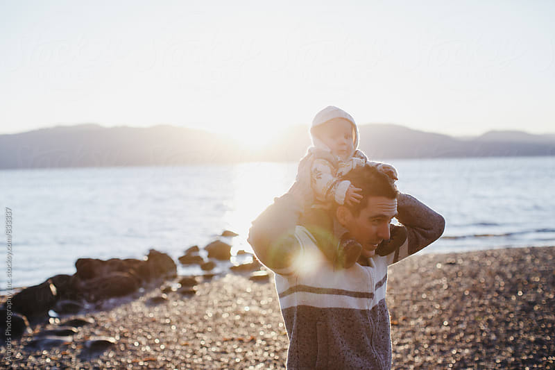 Young dad giving baby boy a shoulder ride at sunset by Rob and Julia Campbell for Stocksy United