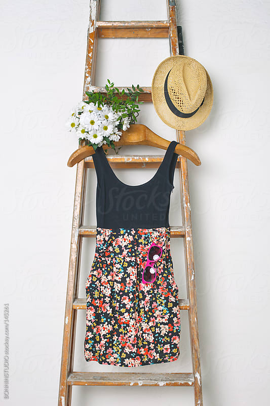 Still life of floral dress, bouquet of daisies and straw hat hanging on staircase. by BONNINSTUDIO for Stocksy United