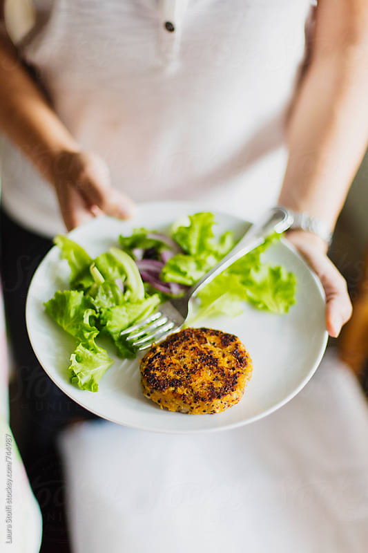 VEgan meal: young woman showing a dish with quinoa and sweet potatoes burger and salad on it by Laura Stolfi for Stocksy United