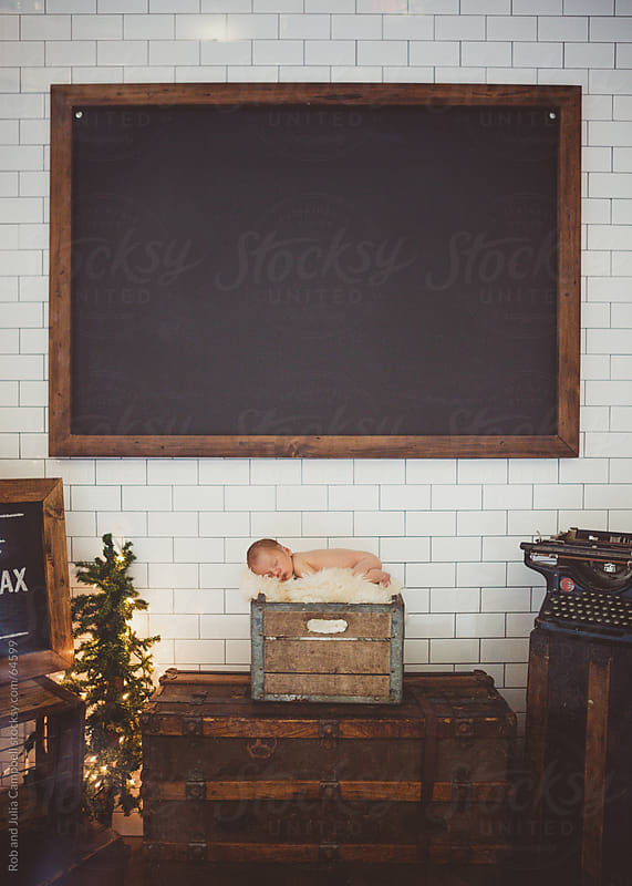 Newborn baby sleeping peacefully with black chalkboard behind by Rob and Julia Campbell for Stocksy United