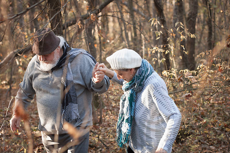 Senior man giving his hand to his wife to help her walking in the forest by Beatrix Boros for Stocksy United
