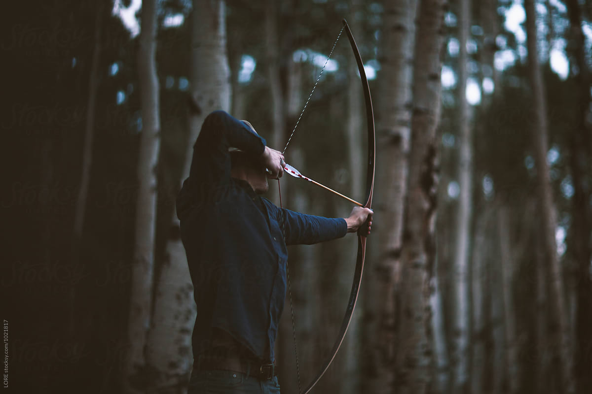 Adult male archer shoots a bow and arrow in aspen forest by