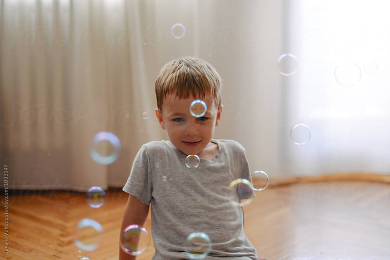 kid is playing with the  bubbles by Jovana Vukotic for Stocksy United