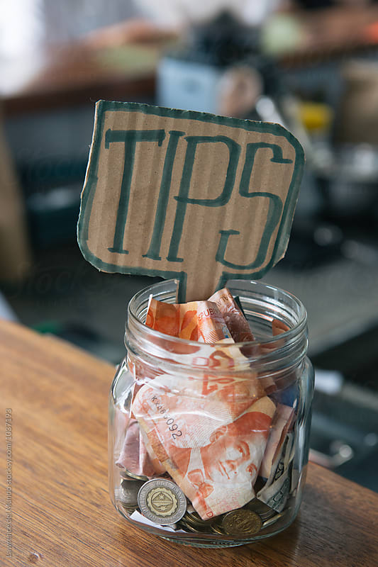 Tip jar full of bills and coins in a coffee shop. by Lawrence del Mundo for Stocksy United