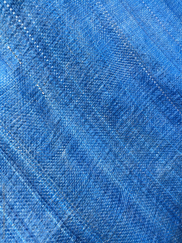 Close up of stretched blue tarpaulin covering industrial fishing equipement by Paul Edmondson for Stocksy United