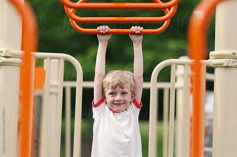 boy playing on a playground by Kelly Knox for Stocksy United