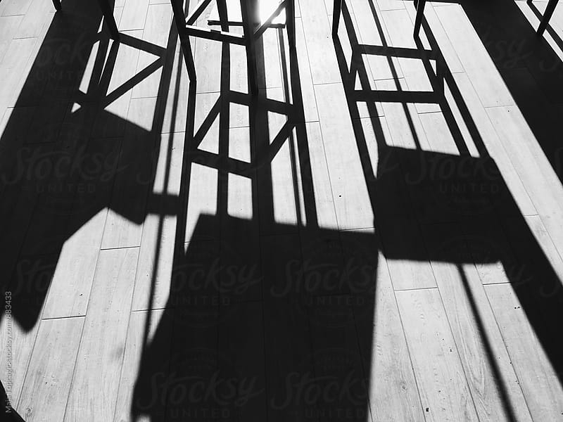 Shadows of chairs on the floor by Maja Topcagic for Stocksy United