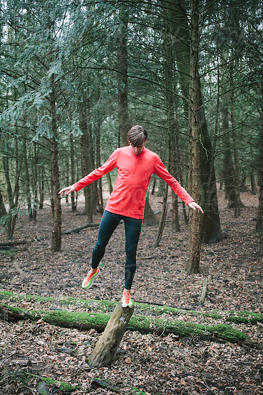 A young runner balancing on a tree trunk in the forest by Ivo de Bruijn for Stocksy United