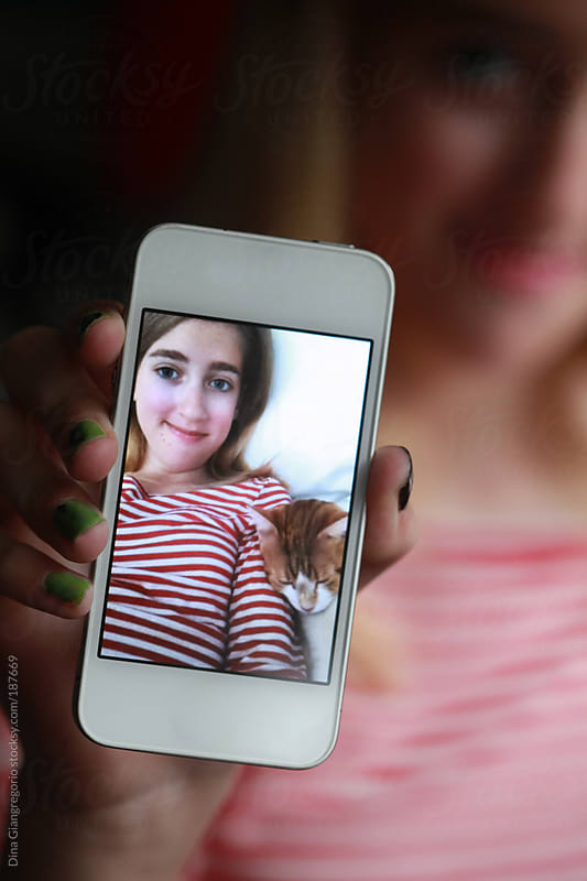 Teenaged girl with colorful nails holding phone showing selfie of her and the cat by Dina Giangregorio for Stocksy United