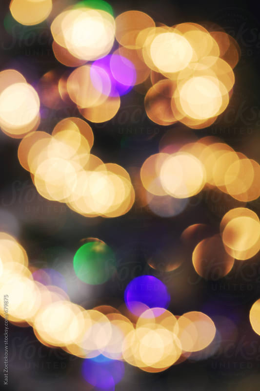 A Christmas tree photographed blurry so as to bring out the unfocused and thus circular shapes of its golden and multi-colored fairy lights.  by Kaat Zoetekouw for Stocksy United