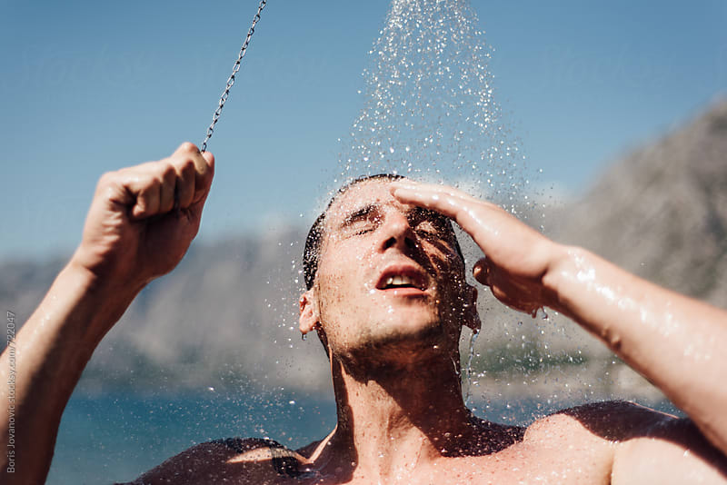 Man having a shower on the beach by Boris Jovanovic for Stocksy United
