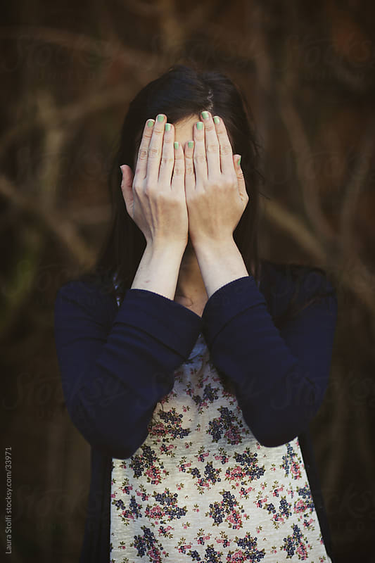 Young woman covering her face with her hands  by Laura Stolfi for Stocksy United