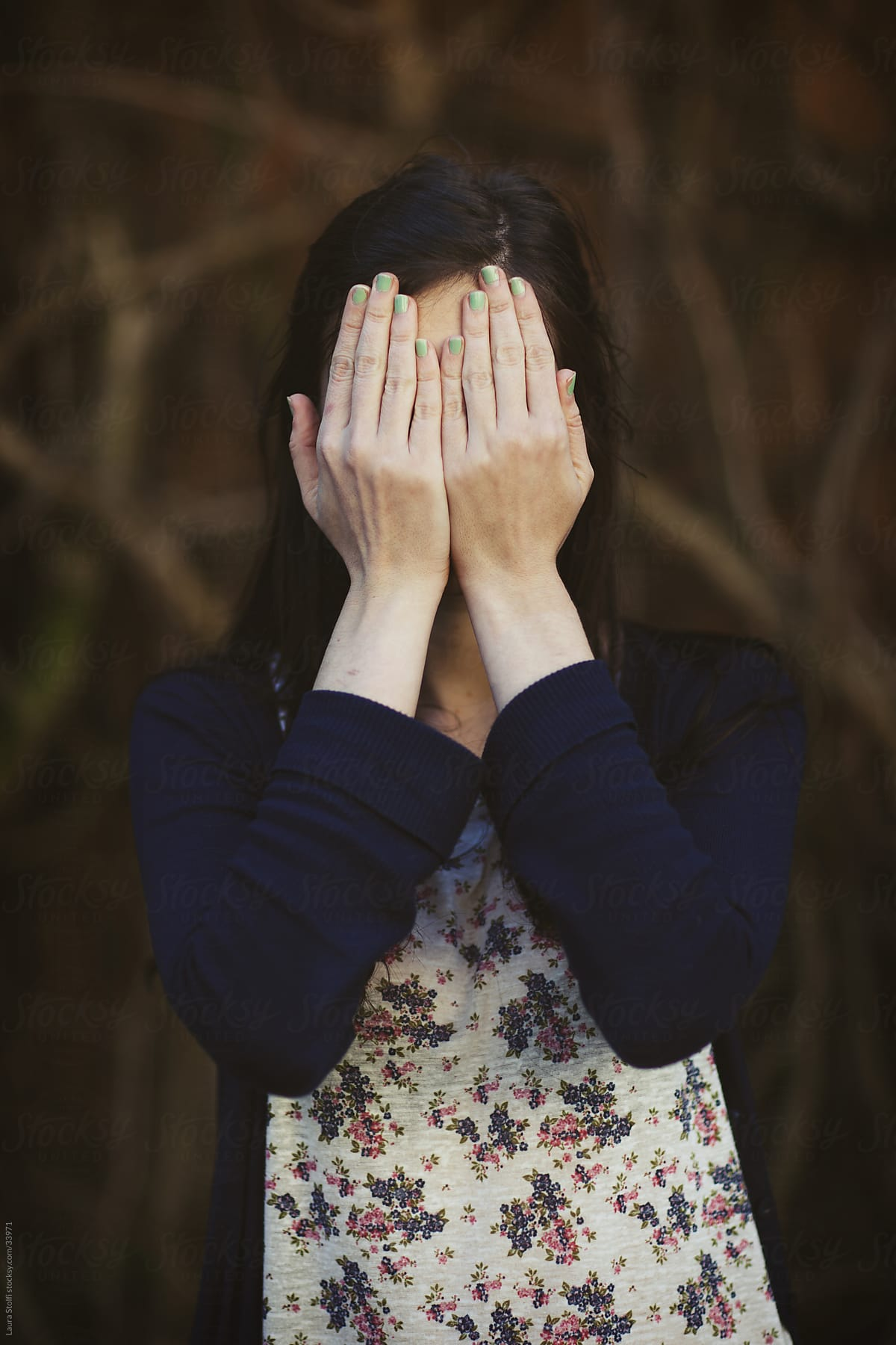 e16f64f7ee05b Stock Photo - Young Woman Covering Her Face With Her Hands