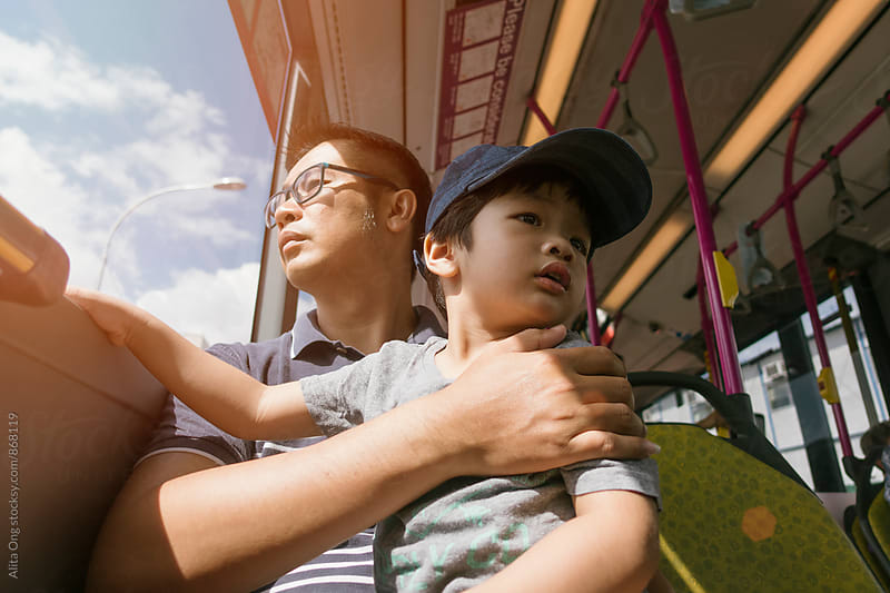 Dad holding son in public transport (bus) by Alita Ong for Stocksy United