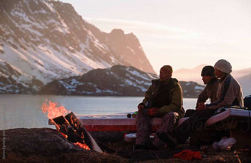 Group of people sitting around a campfire in the mountains by the ocean by Soren Egeberg for Stocksy United