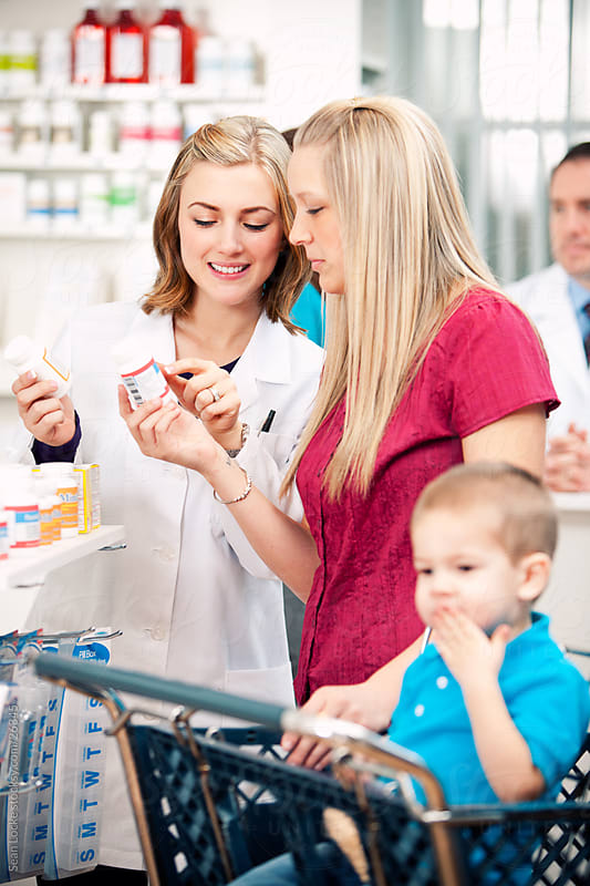 Pharmacy: Pharmacist Helps Customer with Medicine by Sean Locke for Stocksy United