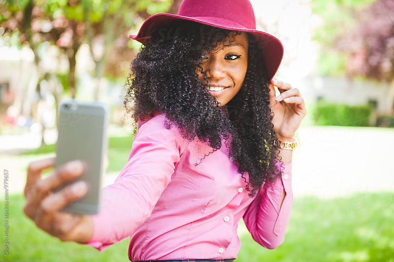 Beautiful Black Young Woman Taking a Selfie with a Mobile Phone at the Park by Giorgio Magini for Stocksy United