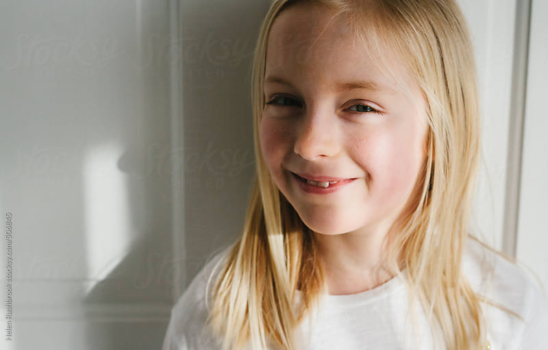 A sunlit little girl looking at camera and smiling. by Helen Rushbrook for Stocksy United