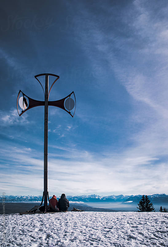 Couple next to Cross during an altitude hiking. Mont Blanc in Background by Gabriel Diaz for Stocksy United