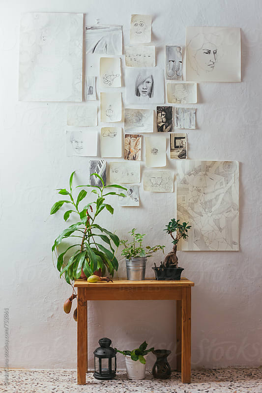 Plants on a wooden table with drawings on a white wall by Giada Canu for Stocksy United