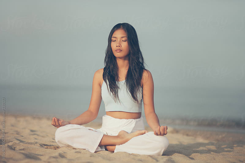 Asian Woman Meditating on Beach by VISUALSPECTRUM for Stocksy United