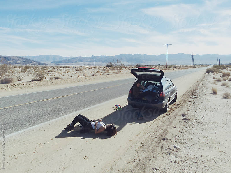 Taking a Rest From Skateboarding on the Side of the Road by Kevin Russ for Stocksy United