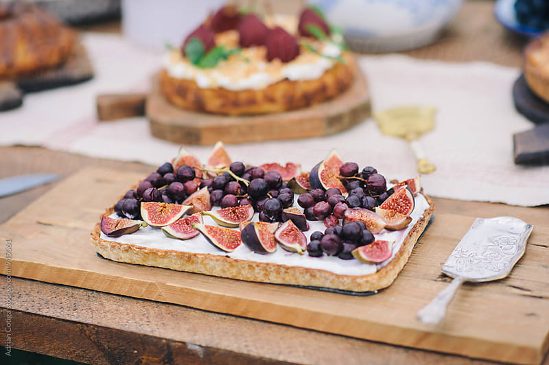 A tart with figs and grapes on a table. by Adrian Cotiga for Stocksy United