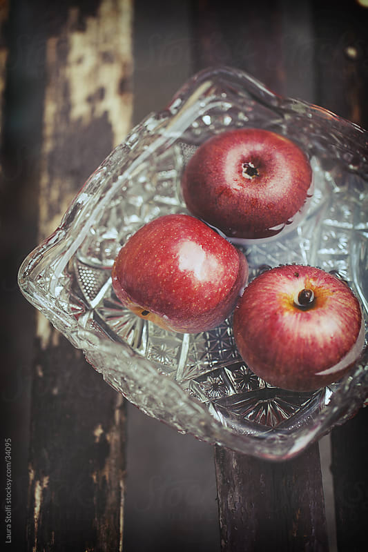 Close-up of red apples floatng in crystal bowl filled with water on wooden bench by Laura Stolfi for Stocksy United