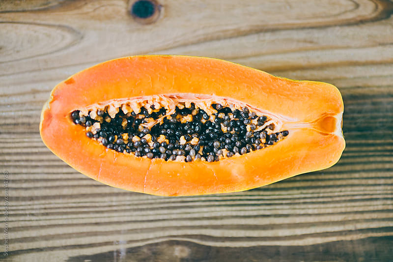 Inside of a Papaya on Wood Background by Stephen Morris for Stocksy United
