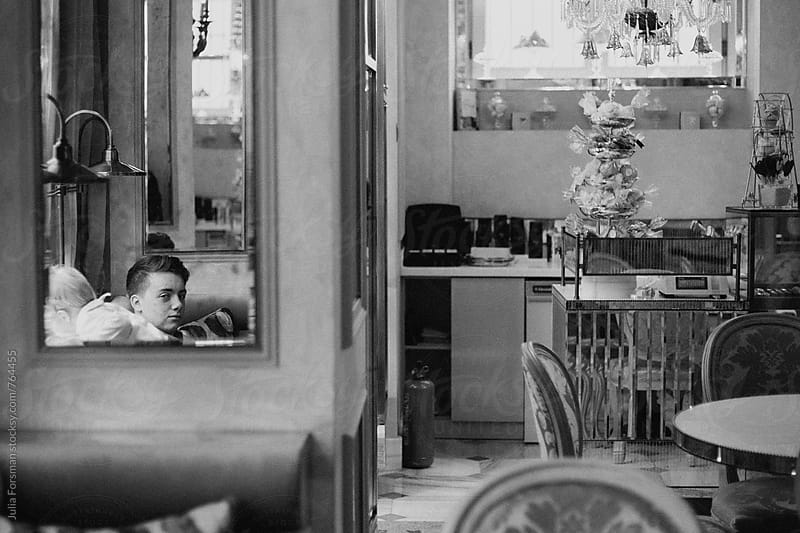 A reflection of a teenage boy in a mirror in a pretty vintage patisserie. by Julia Forsman for Stocksy United