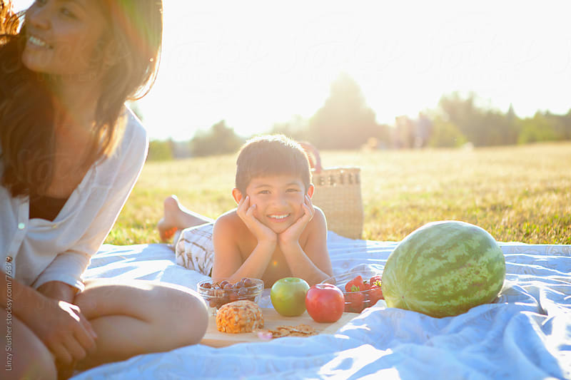 Smiling boy lying on picnic blanket with family by Linzy Slusher for Stocksy United