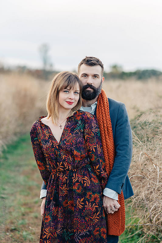 Beautiful and stylish couple standing in a field by Jakob for Stocksy United