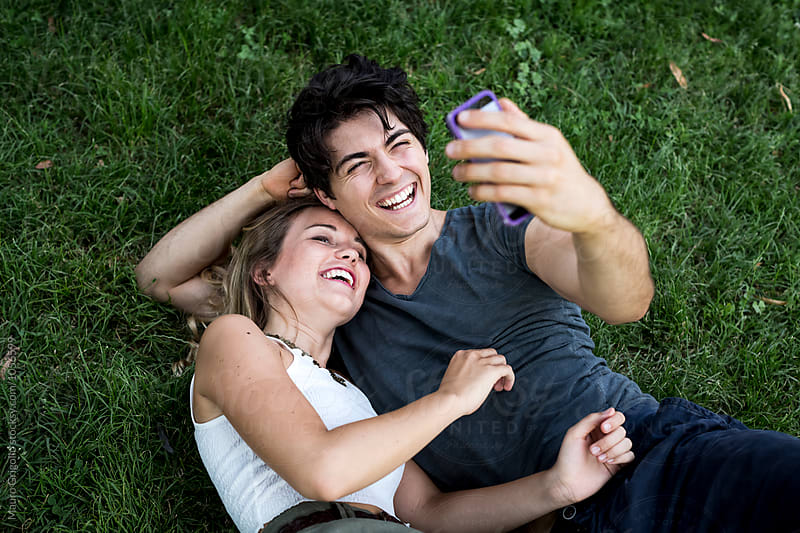 Couple taking a selfie at the park by Mauro Grigollo for Stocksy United