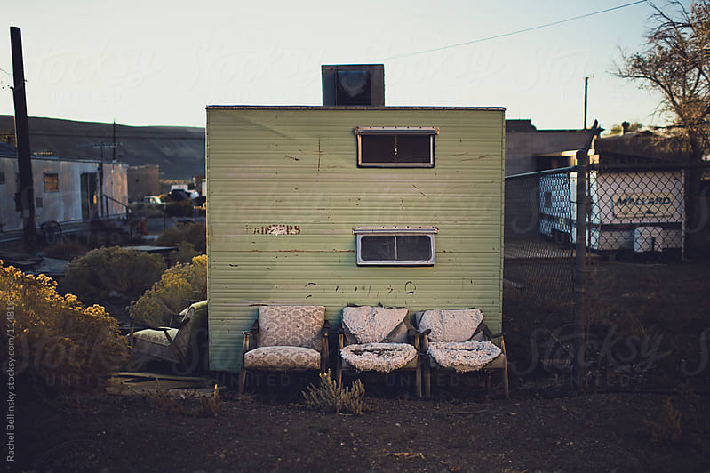 Three ratty chairs in front of an abandoned trailer by Rachel Bellinsky for Stocksy United