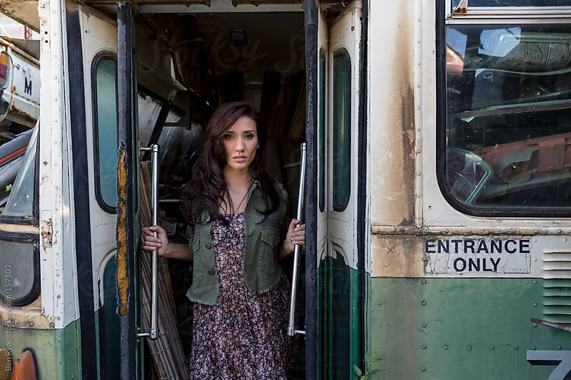 Young mixed race woman standing in the doorway of a derelict bus by Ben Ryan for Stocksy United