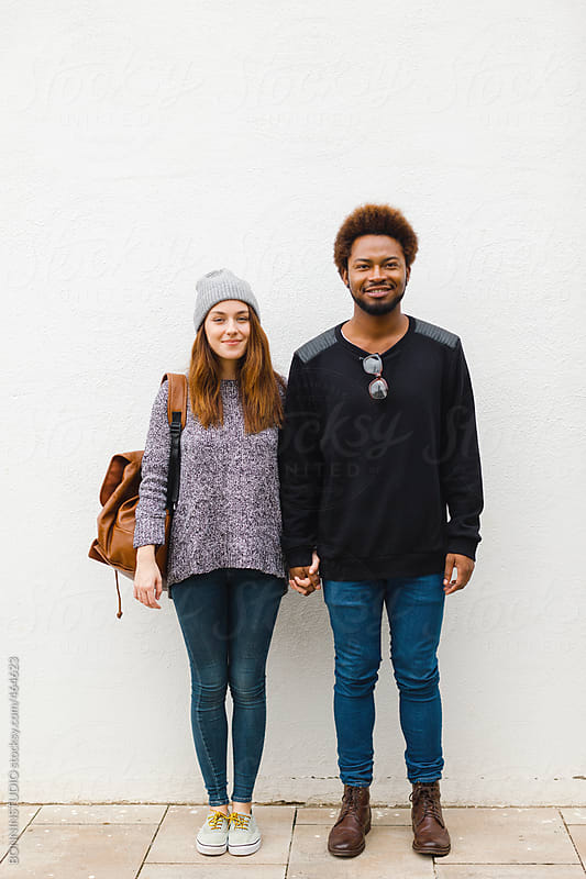 Portrait of young multi ethnic couple standing on white background. by BONNINSTUDIO for Stocksy United