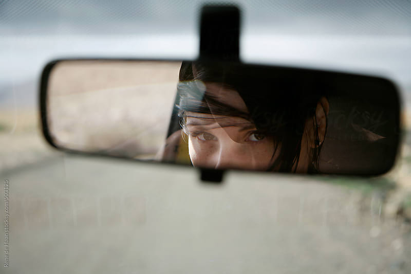 young woman looking in mirror of car by Rene de Haan for Stocksy United