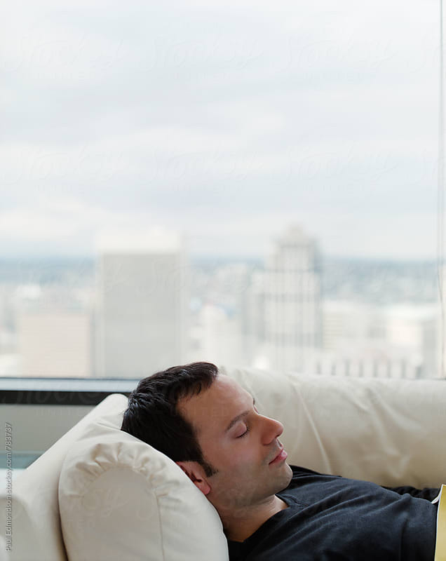 Male business executive sleeping on soft couch by window by Paul Edmondson for Stocksy United