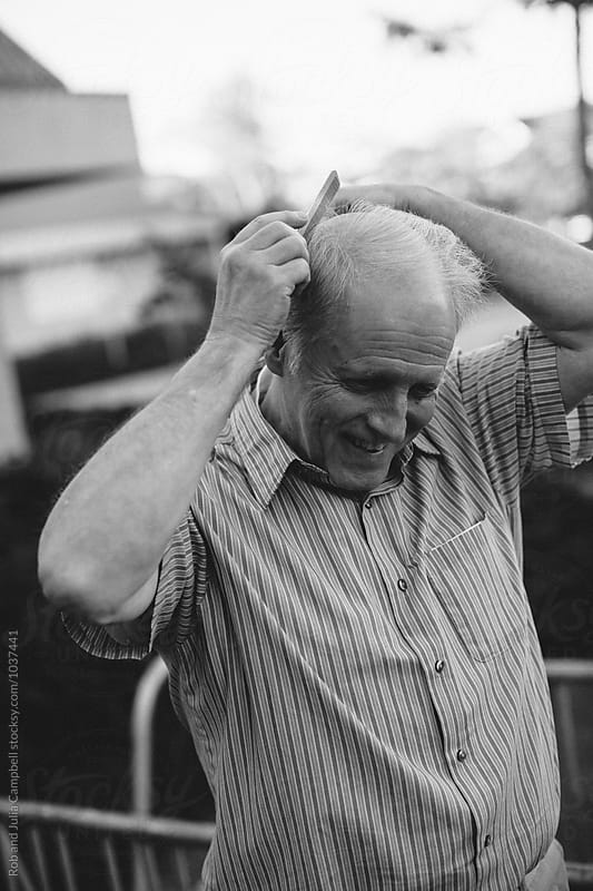 Happy, caucasian senior man combing hair outside  by Rob and Julia Campbell for Stocksy United