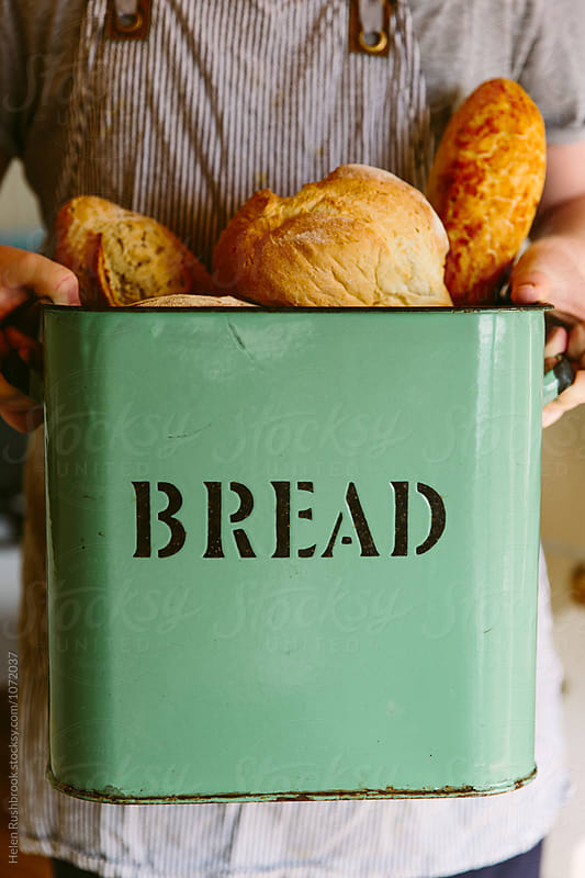 Person holding a vintage bread bin full of loaves of bread.  by Helen Rushbrook for Stocksy United