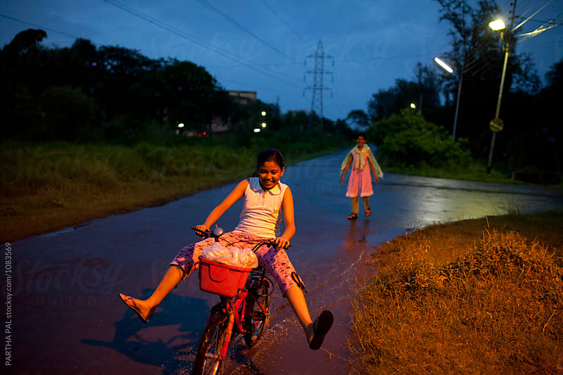 Teenage girl plying with cycle in blue hour by PARTHA PAL for Stocksy United